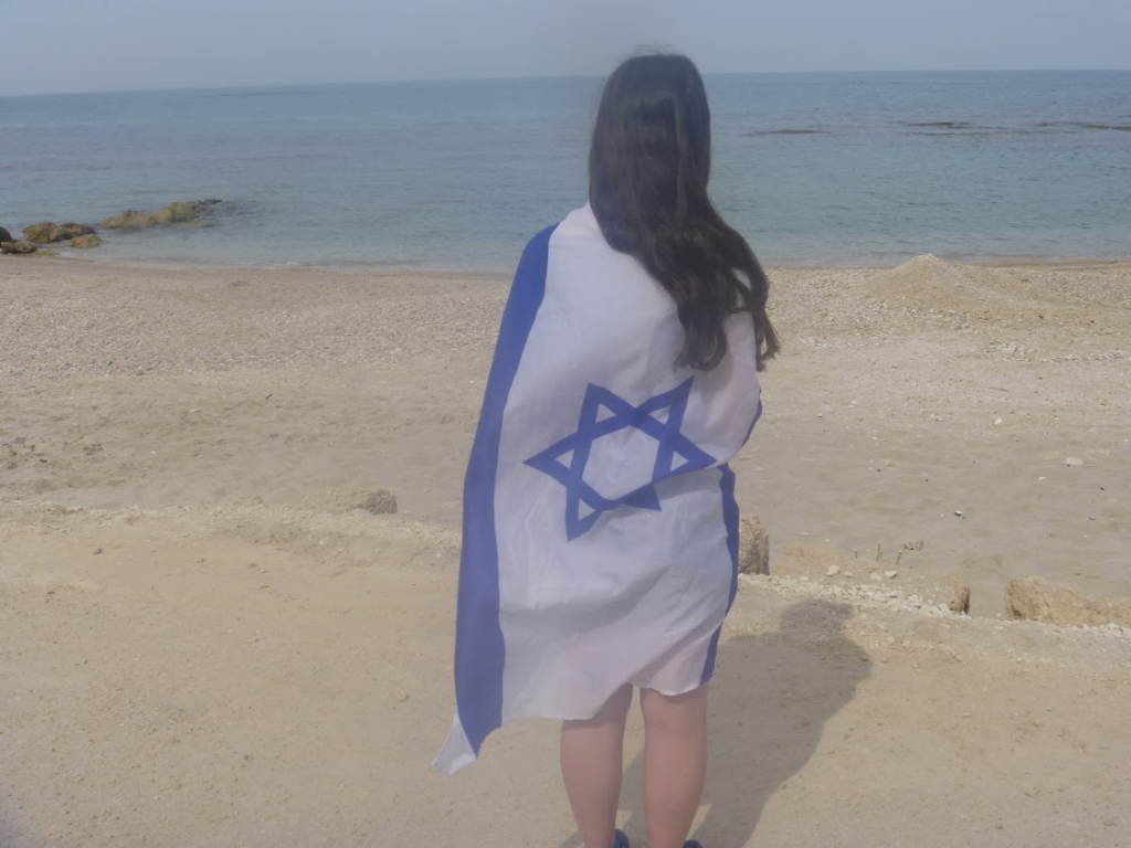Jewish teen female with Israeli flag on beach in Israel Caesarea