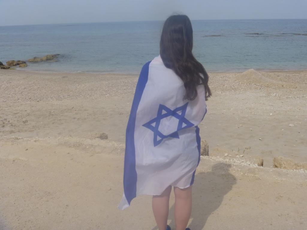 Jewish teen female with Israeli flag on beach in Israel Caesarea